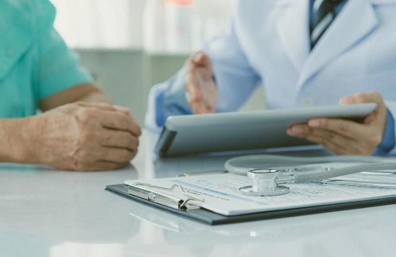 دکتر در مورد بیماری پارکینسون با فرد بیمار در حال صحبت کردن است